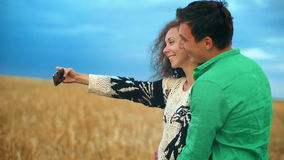 Young couple taking selfie in the wheat field. Two friends having fun outdoor. Smiling on the camera. Slow motion stock video