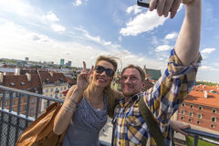 Young couple taking selfies on a smartphone on the background of the Castle Square in Warsaw. Stock Images