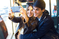 Young couple taking selfies with smartphone at bus. Royalty Free Stock Image