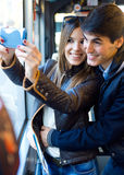 Young couple taking selfies with smartphone at bus. Stock Images