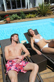 Young couple taking sun by the pool Royalty Free Stock Photo