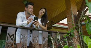 Young couple talk holding cell smart phone on balcony in hotel, happy man and woman surfing internet together stock video