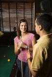 Young couple talking at bar. Young man and woman talking and smiling while playing billiards Royalty Free Stock Photo
