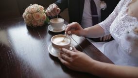 Young couple talking and drinking coffee during breakfast at cafe. They mixing sugar in cappuccino. Close up shot of hands stock video footage