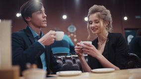 Young couple talking and drinking coffee on a date in a modern restaurant. Young couple talking and drinking coffee on a date in a modern restaurant stock footage