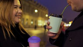 Young couple are talking and drink coffee at night illuminated street background. Young couple are talking and drinks coffee at night illuminated street stock video