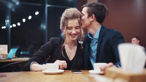 Young couple talking freely, laughing happily, kissing and enjoying each other, then looking at phone's screen in stock video footage