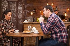 Young couple talking about the future in a cozy vintage pub. Night out royalty free stock image