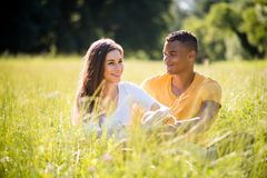 Grassfield date - couple together in nature. Young couple talking in grassfield on summer sunny day Royalty Free Stock Photos