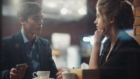 Young couple talking lively, drinking coffee having a date in a nice new modern café in city center. stock footage