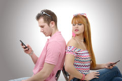 Young couple talking on mobile phones sitting back to back. Royalty Free Stock Photos