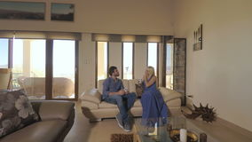 Young couple talking and relaxing on the sofa in room stock video
