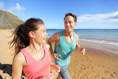Young couple talking running on beach jogging Stock Images