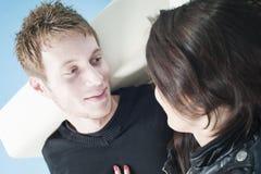 Young couple talking on a sofa Stock Photos