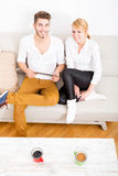 Young couple talking on the sofa Royalty Free Stock Photography