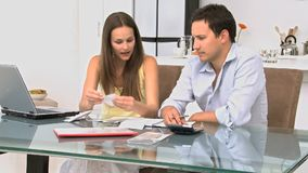 Young couple talking about their debts at a table stock footage