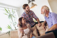 Young couple talking with their senior father. At home stock images