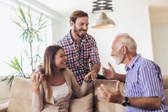 Young couple talking with their senior father. At home stock photo