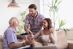 Young couple talking with their senior father. At home stock photos