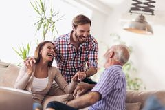 Young couple talking with their senior father. At home stock image