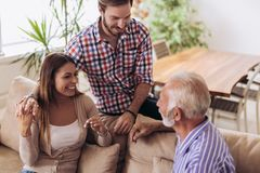 Young couple talking with their senior father. At home royalty free stock photography