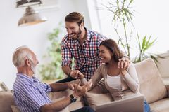 Young couple talking with their senior father. At home royalty free stock image