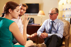 Young Couple Talking To Male Counsellor. Discussing Relationship Difficulties royalty free stock image
