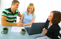 Young Couple Talking To Real Estate Broker royalty free stock image