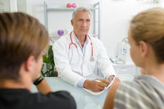 Young couple talking to senior doctor. Couple stock photo