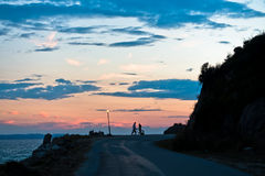 Young couple with tandem bicycle at sea coast after sunset Stock Images