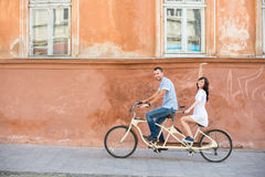 Young couple on tandem bicycle at the street city Stock Photos