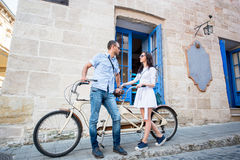 Young couple on tandem bicycle at the street city Stock Photography