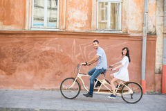 Young couple on tandem bicycle at the street city Stock Images