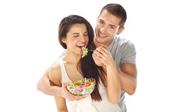 Happy couple eating salad together on a white background Stock Photos