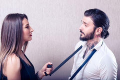Young couple teasing each other. Sexy heterosexual couple iteasing with each other on grey background Royalty Free Stock Photography