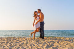 Young couple teasing one another at the beach Stock Photos