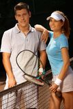 Young couple on tennis court smiling Stock Images