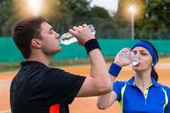 Young couple of tennis players drinking water on clay court outd. Young couple of tennis players wearing a sportswear drinking water after match outdoor on clay Stock Photos
