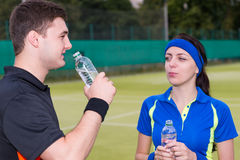 Young couple of tennis players drinking water after match outdoo Stock Photo