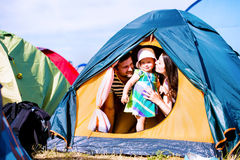 Young couple with their baby daughter in tent, summer Stock Image