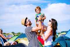 Young couple with their baby daughter between tents, summer Stock Photo