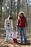 Young couple with their baby in the forest. Young couple with their baby walking in the forest Stock Photography