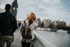 Young couple in their backs, walking by Westminster Bridge, with Thames River and Big Ben in the background, in London, England. LONDON, ENGLAND - 25th October royalty free stock images