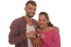 Young couple with their piggy bank Royalty Free Stock Images