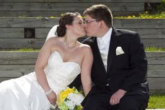 Young couple on their wedding day. A young couple shares a kiss on their wedding day Stock Images