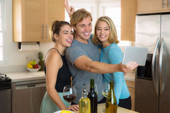 Young couple and third wheel having fun at home pose for a selfie picture to share on their social network. Group of friends have fun at home as a group party royalty free stock photo