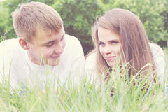 Young couple, tinted. Portrait of a young couple lying green grass Royalty Free Stock Photo