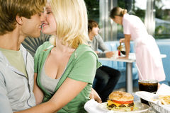 Young couple about to kiss, sitting in a diner Royalty Free Stock Images