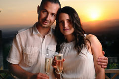 Young couple toast looking ahead at sunset Stock Photography