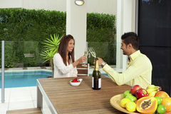 Young couple toasting with champagne. In a modern backyard Stock Photo